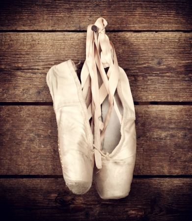 pointe: Old used pink ballet shoes hanging on wooden background