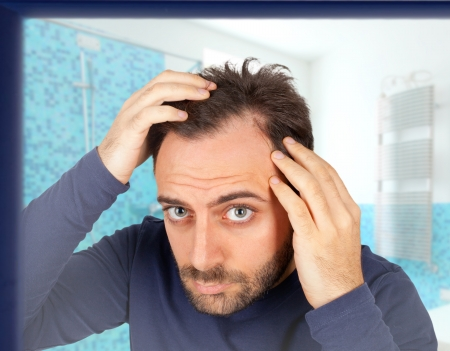 Caucasian young man controls hair loss in the bathroom