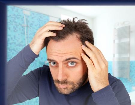 Kaukázusi fiatalember ellenőrzi hajhullás a fürdőszobában