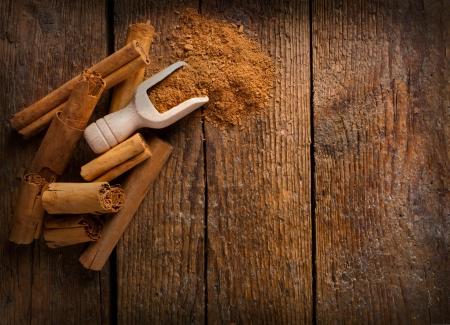 cinnamomum: Frame with sticks and ground ceylon cinnamon on wooden table