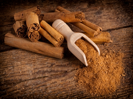 wood stick: Sticks and ground ceylon cinnamon with wood spoon on wooden table Stock Photo