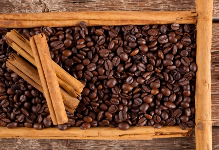 ceylon: Frame with coffee beans and ceylon cinnamon on wooden table Stock Photo