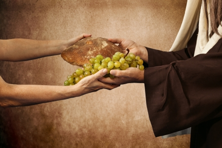 Jesus gives bread and grapes on beige background photo