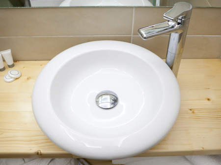 Round white sink in modern bathroom on wooden shelf photo
