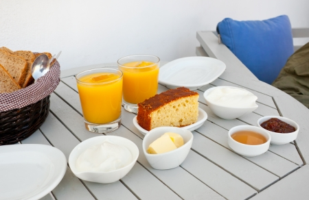 Traditional Greek breakfast with ogurt, orange juice, cake, jam, honey and bread  photo