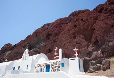 fira: Traditional chapel with Greece flag in red beach, Santorini
