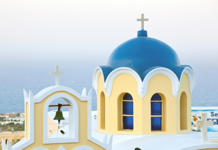 Traditional blue cupola with yellow church in Thira, Santorini, Greece  photo