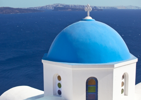 Traditional church with blue cupola at Oia Village, Santorini island in Greece  photo