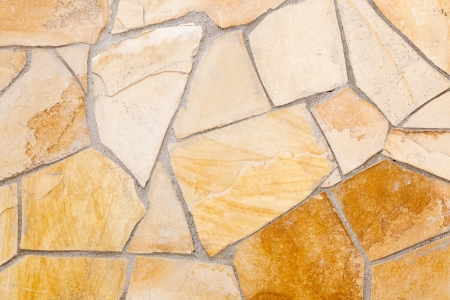 Wall lined with light yellow porphyry stones Imagens
