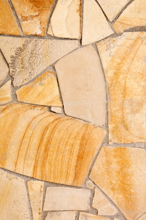 Wall lined with light yellow porphyry stones photo