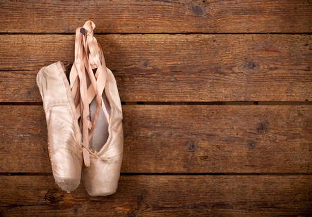 Old used pink ballet shoes hanging on wooden background photo