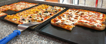 square cut: Counter of the pizzeria with trays and square pieces of pizza