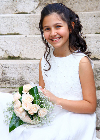Smiling young girl in white dress for First Communion photo