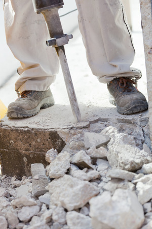 Worker demolishing the concrete with a jackhammer. Stock Photo