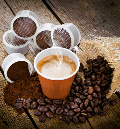 Espresso coffee in disposable cup with pods on wooden table Editorial