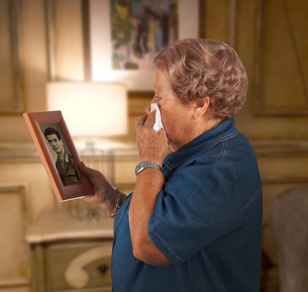 deceased: Old lady crying watching a photo of a deceased person.