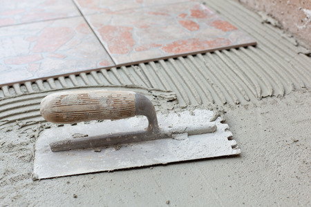 notched: Notched spatula for applying adhesive for tile.
