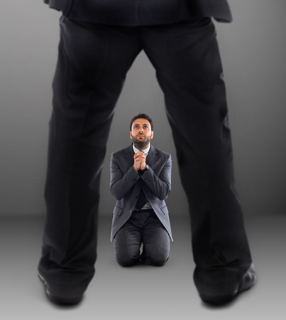 Young business man on his knees praying not to be dismissed. photo