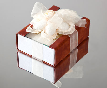 personally: The gift box with a brown cover is wrapped up by a beige tape with a bow. Stock Photo