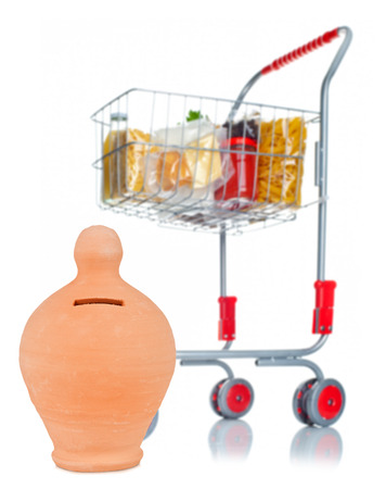 Shopping cart full with money box and food products on white background photo