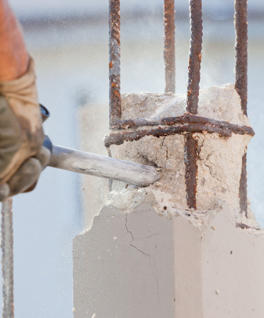 Workers break reinforced concrete with jackhammer at a construction site photo