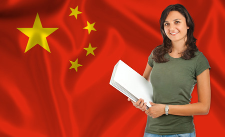 Young female student smiling over Chinese flag photo