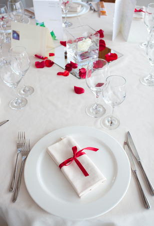 Table set for a Wedding reception with red decorations. photo
