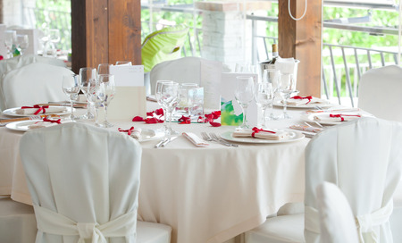 Table set for a Wedding reception with red decorations.