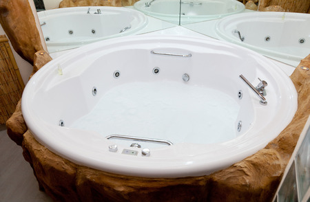 White whirlpool bath with rock ready to take a bath. photo