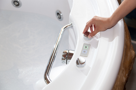White whirlpool bath with rock ready to take a bath.