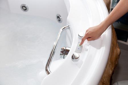 hydromassage: White whirlpool bath with rock ready to take a bath.