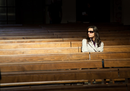 supplicate: Woman praying in church and looks invisible presence to his right.