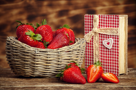 basketful: Beautiful strawberries with cookbook on wooden table