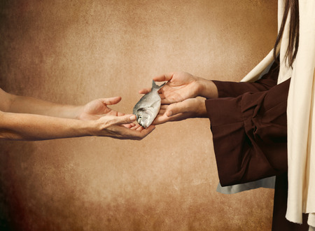 Jesus gives the fish to a beggar on beige background photo