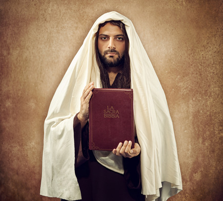divinity: Jesus shows the holy bible on old beige  Stock Photo