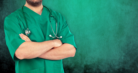 Close up of a doctor with his arms crossed on green background. Stock Photo - 27247475