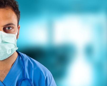 doctoring: Close up di giovane medico di sesso maschile che guarda alla telecamera in ospedale.