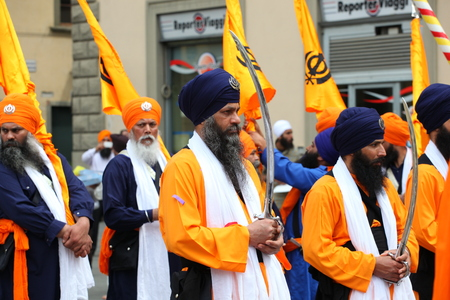 SAN GIOVANNI VALDARNO, ITALY - APRIL 15, 2014: NagarKirtan, Indian religious procession celebrated in different parts of Italy and the world. All participants wear traditional dress and turban with the emblem of the Sikh faith.