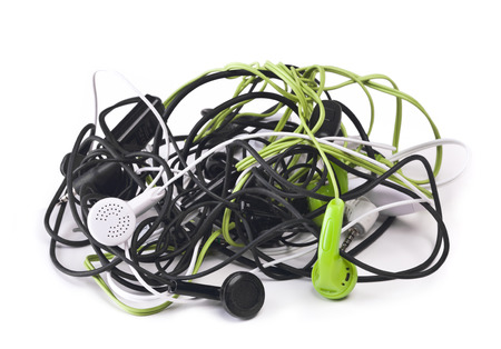 Twisted headphones, of different colors, on white .