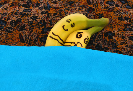 romantic sex: Bananas hugging each in bed. He is happy, she is sad.