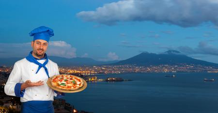 Cocinero joven con la pizza margherita napolitano con Golfo de Nápoles, en el fondo.
