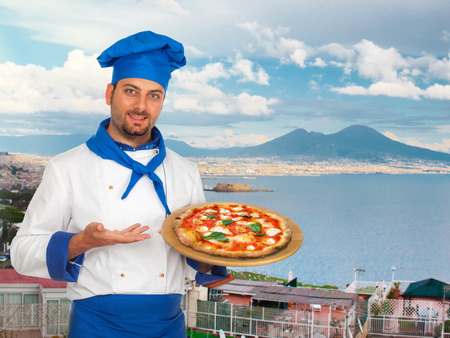 Young chef with neapolitan pizza margherita with Gulf of Naples in background. Фото со стока