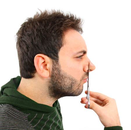 long nose: Concept of cosmetic surgery. Boy symbolically cutting the nose with scissors. Stock Photo