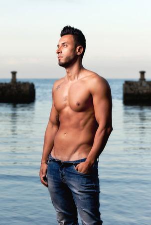 Hombre musculoso guapo joven en la playa de grava.