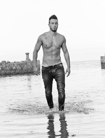 Young handsome muscular man on the stony beach. photo
