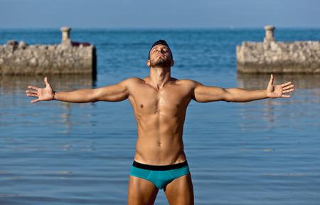 石のビーチで水着で若いハンサムな筋肉男。