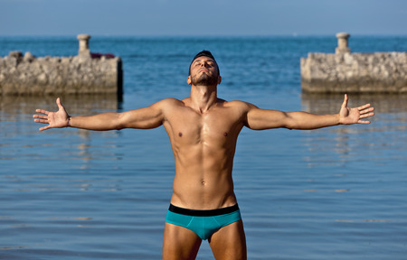Young handsome muscular man in swimsuit on the stony beach.