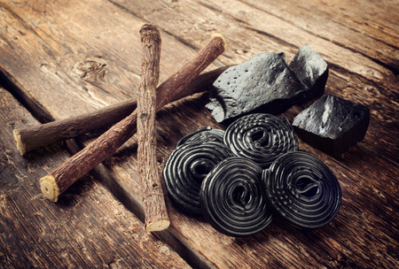 Production steps of licorice, roots, pure blocks and candy on wooden table Stock fotó