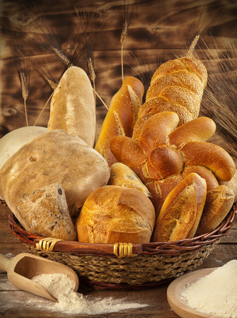 Wicker basket with different types of bread on wooden table. photo