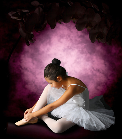 Ballerina tying ribbons pointe on purple background photo
